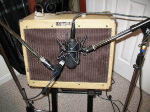 Photo of a guitar amp with mics in front of it ready to record