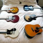 Six guitars of different styles and colors laid out on a white bed
