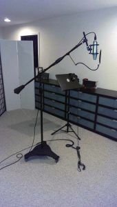 Photo of Neumann U87 on a mic stand in a large live tracking room at Beach House Studios