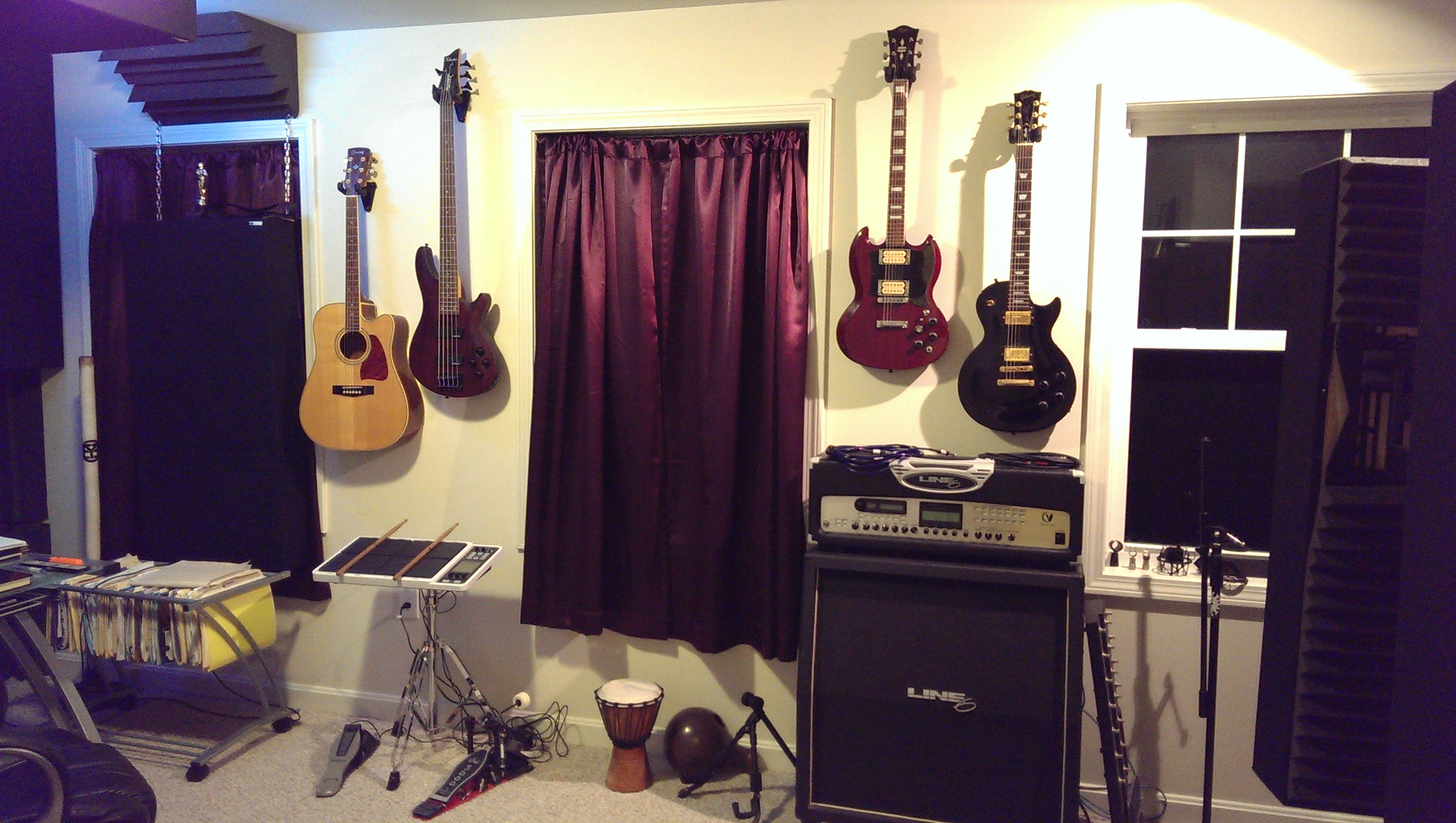 Four guitars hung on the wall of a recording studio