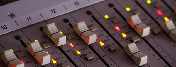 close up photo of faders on a mixing board